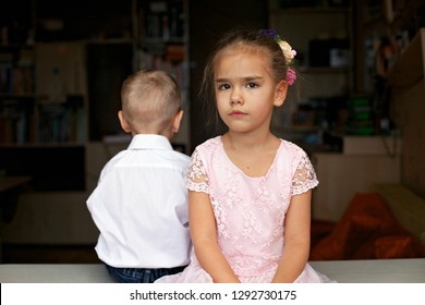 Little boy in white shirt and beautiful little princess wearing pink dress sitting together back to back, they are sad, love and problem concept