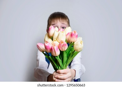 Little boy in white shirt gives a bouquet of tulips on light background