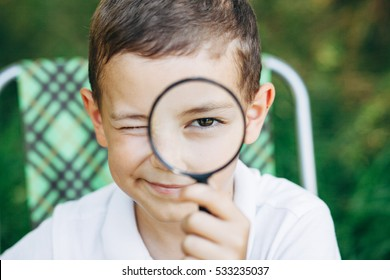 Little boy in white shirt looking through magnifying glass in the garden