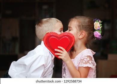 Little boy in white shirt and soft pink bow-tie and beautiful little princess wearing soft pink dress kissing behind a red heart, they fall in love, romantic and love concept, Valentine Day greeting