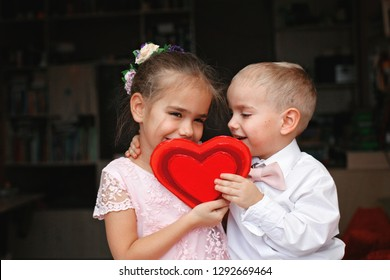 Little boy in white shirt and soft pink bow-tie and beautiful princess wearing soft pink dress kissing behind a red heart, they fall in love, romantic and love concept, Valentine Day greeting