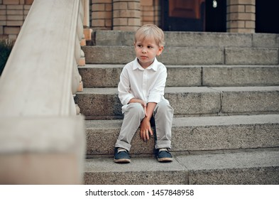 The little boy in a white shirt and trousers sits on steps