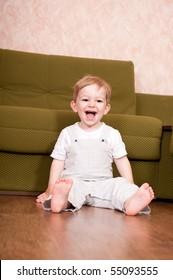 Little boy in white is sitting near sofa