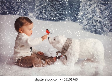 little boy in white sweater sitting  in the winter forest  and playing with a toy polar bear and bird