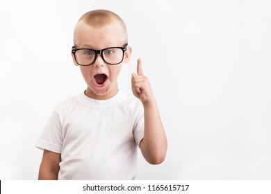 Little boy in a white T-shirt and black glasses raises his finger up on a background, symbolizing the emergence of a new idea. smart kid