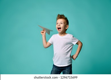 Little boy in white t-shirt and blue jeans casual play brave pilot hero. he ready to launch a paper plane looks up to sky and shouts on popular green. take-off.