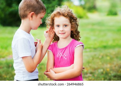Little boy in white t-shirt whispers a girl in red dress.