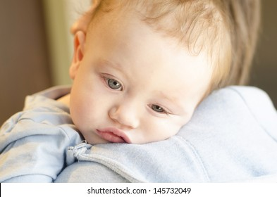 A little boy who is not feeling well on his parents shoulder
