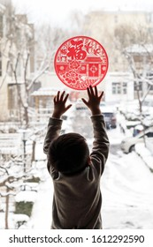 The little boy with the window print(Translation:blessing,Fook lam moon,Good luck,Bamboo to report the safety of thousands,Flowers and wealth usher in the New Year.)