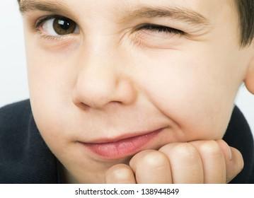 Little boy wink of an eye. Close up studio shot