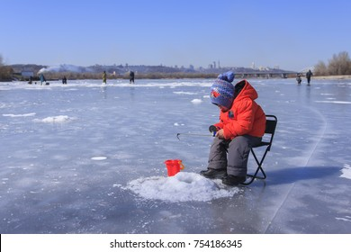 a little boy in winter clothes is fishing on a frozen lake