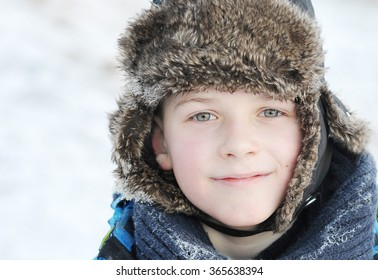 little boy in winter a fur hat in winter - snow on the scarf and hat