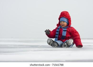 Little boy in winter on ice