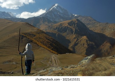 Little boy with wooden stick standing on background of incredible snowy Mount Kazbek and brown hills at autumn time, small travler and discoverer, Georgia