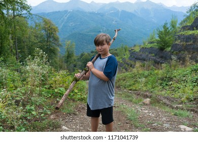 Little boy with wooden stick standing on background of Mount and brown hills at autumn time, small travler and discoverer.