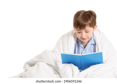Little boy wrapped in blanket reading book on white background