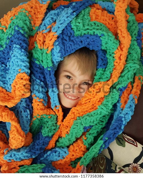 Little boy wrapped up in a cozy orange, blue, and green hand knit blanket.