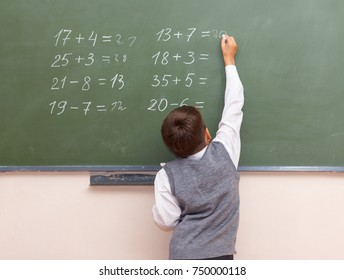 A little boy writes with chalk on a blackboard.