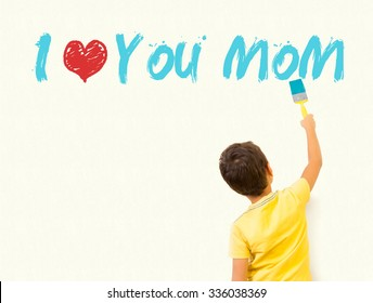 "Little boy writing ""I Love you mom"" with painting brush on wall background"