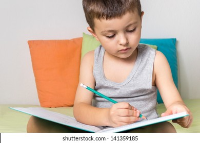 Little boy writing with pencil