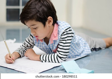 Little boy writing white paper on the floor