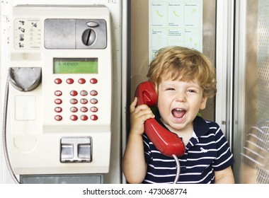A little boy yelling into the phone. Kid screaming into the red telephone handset