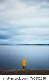 Little Boy in Yellow Rain Coat standing still, looking out over an Rainy autumn Lake: He his ready to take on the world and any adventure that comes his way