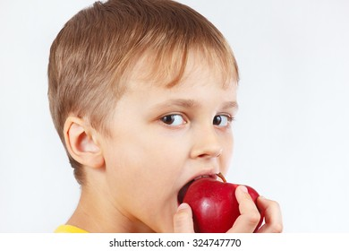 Little boy in a yellow shirt eating a ripe red apple
