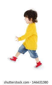 Little boy in yellow shirt walks isolated on white background.