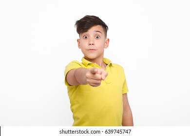 Little boy in yellow t-shirt looking surprised and pointing at camera on white background.