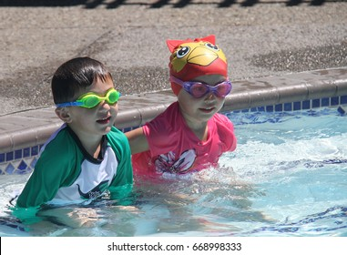 Little boy/girl twins ready to swim in pool