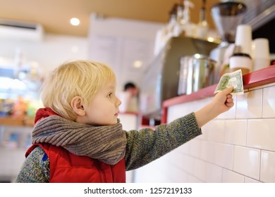 Little boypay off currency note. Kids and money concept. Training in handling money.