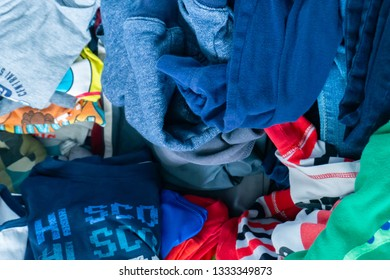Little boy's clothing pile representing clothing donation, kid's drawer, cleaning up, pile of clothes, disorganization and cleaning up.