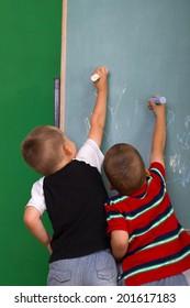 Little boys drawing on a chalkboard.