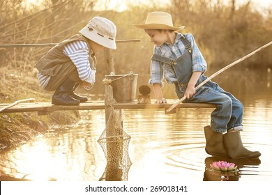 Little boys is fishing at sunset on the lake