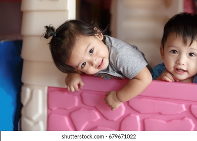 Little boys and girls are having fun in a toy house.