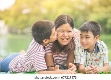 Little boys kissing his single mom at the park