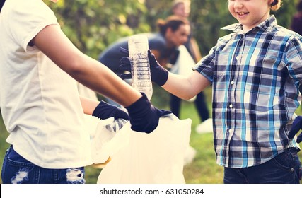 Little Boys Picking Up Plastic Bottle in The Park Volunteer Community Service