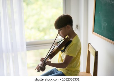 Little boys play and practice violin in the music class room