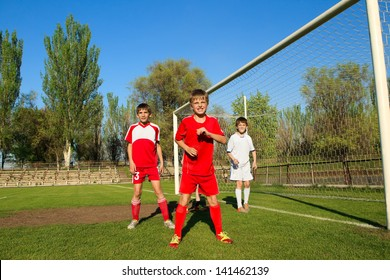 Little Boys playing soccer on the sports field next to goal