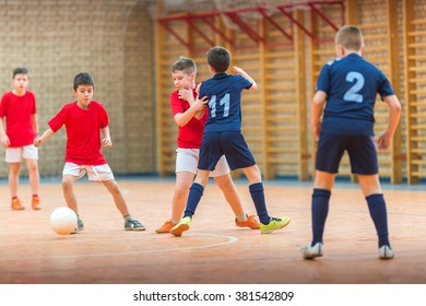 Little Boys playing soccer on indoors