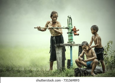 Little boys shower form the traditional Groundwater pump by Grandfather,Grandfather and grandson shower outdoor from Groundwater pump,Happy family in countryside thailand.