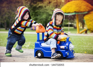 Little boys in the summer, one sitting on a toy car and the other pushed him, dressed in colorful knitted jackets with hoods.
