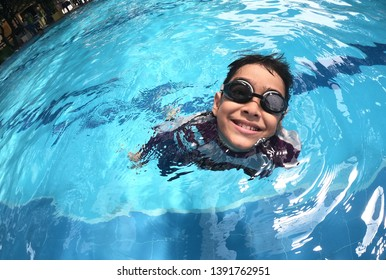 Little boys swimming and diving at the pool under water shot