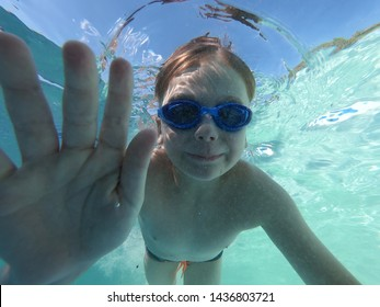Little boys swimming and diving at pool under water shot. Underwater boy dived to bottom of pool. Little boy swims underwater in pool, smiling, blowing bubbles looking at me. Close-up. Horizontal