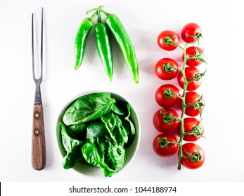 Little branch of cherry tomatoes, bowl of spinach and wooden handle fork over white isolated background.