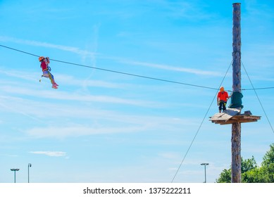 Little brave caucasian 7 years old girlie using a zip line in a rope playground structure in 5 meters high altitude. An indefinited man lend a helping hand.