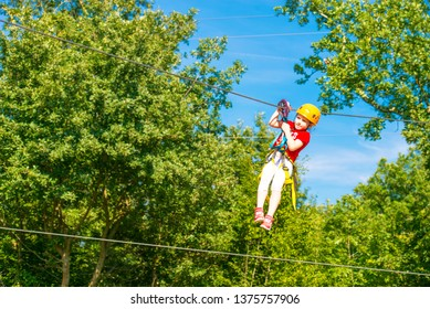 Little brave caucasian 7 years old girlie using a zip line in a rope playground structure in 5 meters high altitude.