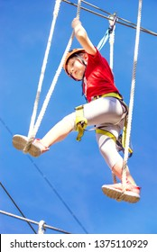 Little brave caucasian girl at outdoor treetop climbing adventure park. 7 years old girlie steps on the ropes in the entertainment park playground structure in 5 meters high altitude