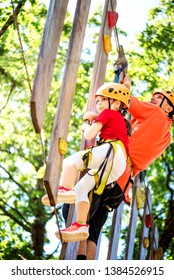 Little brave caucasian girl at outdoor treetop climbing adventure park. 7 years old girlie overcome obstacles on the rope path in the air